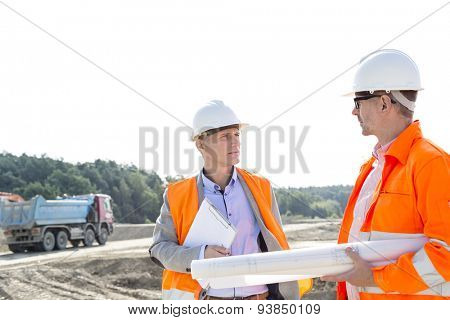 Engineers discussing at construction site against clear sky