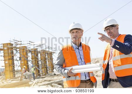 Male engineers discussing at construction site against clear sky