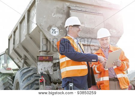 Happy architects discussing over clipboard by construction truck