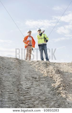 Low angle view of architect showing something to colleague at construction site against sky