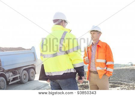 Engineers discussing at construction site against clear sky on sunny day