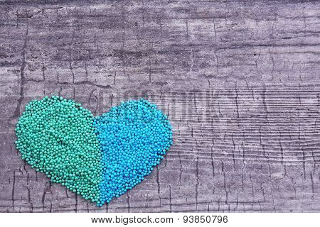 Colorful beads in heart shape on wooden background