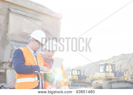 Engineers using laptop at construction site against clear sky
