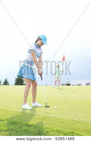 Woman playing golf with female friend holding flag against sky