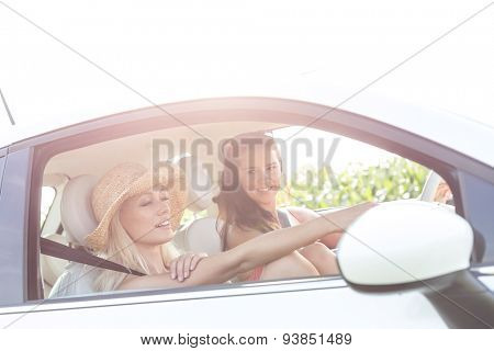 Young female friends in car on sunny day against clear sky
