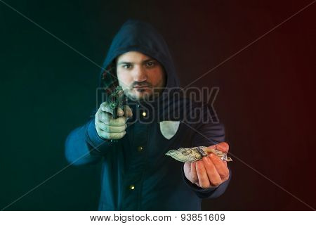 A Person In A Hoodie Is Aiming And Holding The Other Hand With The Dollar Note. A Concept Of The Rob
