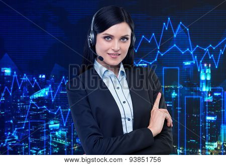 Portrait Of Brunette Support Phone Operator With The Headset. Financial Charts On The Background.
