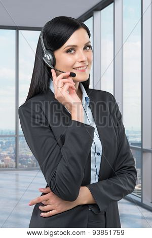Portrait Of Brunette Support Phone Operator With The Headset. New York Panoramic Office On The Backg