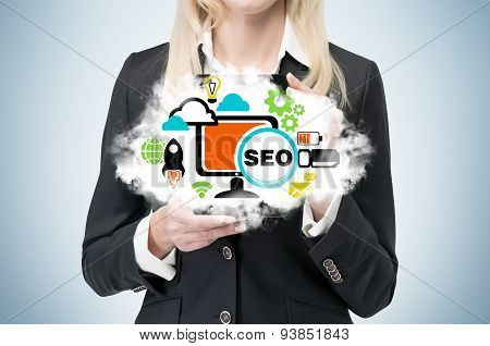 Blonde Businesswoman Is Holding A Cloud As A Metaphor Of 'seo'