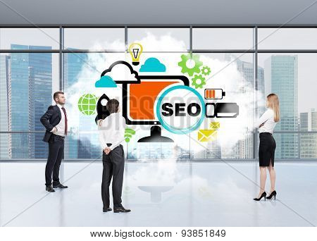 Three Persons In An Office Are Tackling With Seo. A Cloud In An Office Space And A Flowchart. Panora