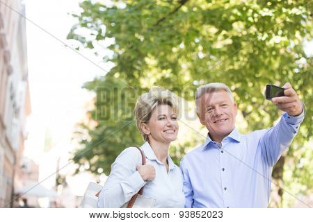 Happy middle-aged couple taking selfie outdoors