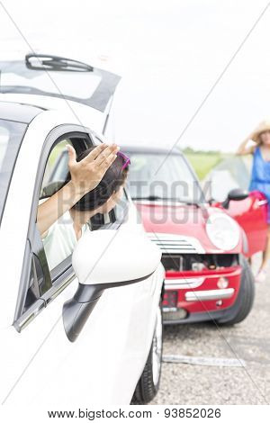Angry woman gesturing while talking to female crashing car on road