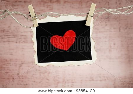 Bright heart on photo paper hanging on rope on wooden background