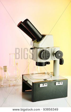 Test tubes and microscope on bright background