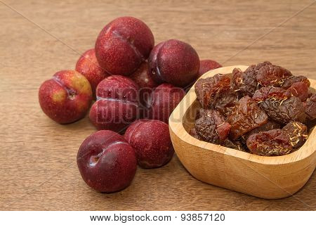 Dried Plums And Fresh Plums On The Wooden Table