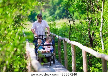 Young Father With Double Stroller In A Park
