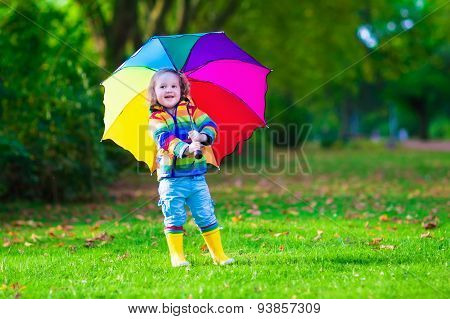 Little Girl Playing In The Rain Holding Colorful Umbrella
