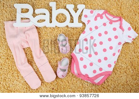 Clothes for baby girl on colorful background