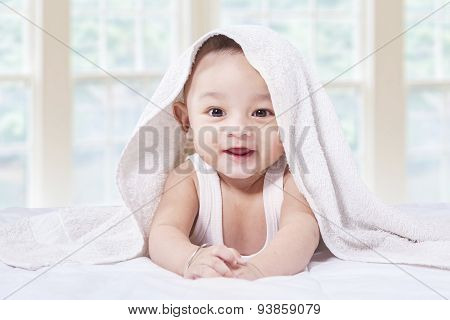 Excited Baby Boy Under Towel On Bed