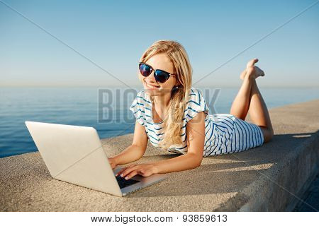 Cheerful Girl Lying On The Beach And Talks To Her Friends On The Laptop Via Wi Fi