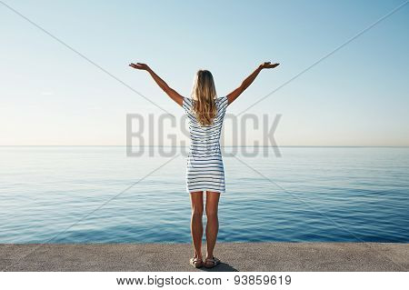 Сheering Young Blond Girl Open Arms At Sunrise At Seaside Beach