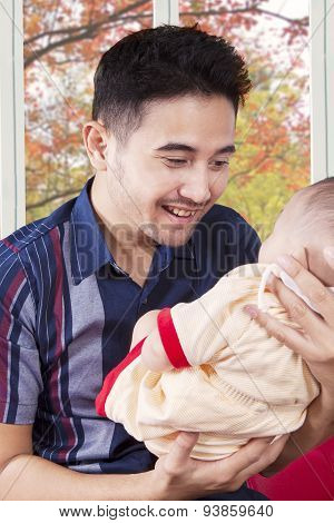 Happy Father Holding His Baby Indoors