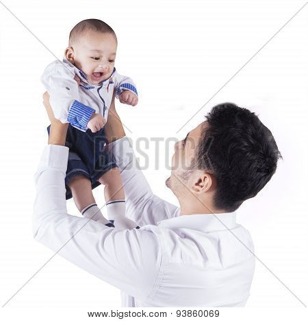 Man Lift Up His Male Infant In Studio