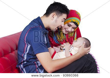 Muslim Parents And Baby On Sofa