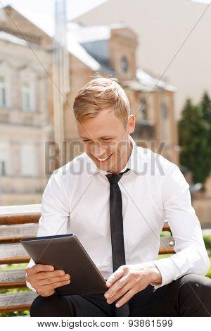Smiling man using tablet outside