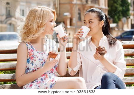 Two girlfriends in park with coffee and cupcakes