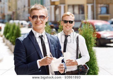 Two  businessman standing with Chinese fast food