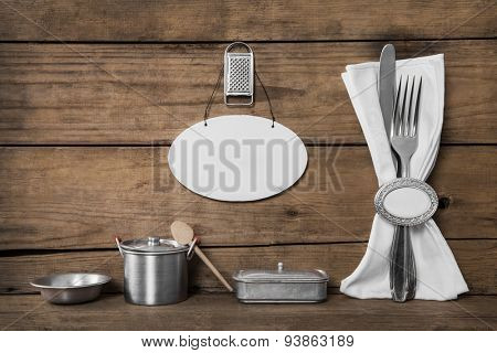 Old wooden background in vintage style with fork and knife and old miniatures for the kitchen.