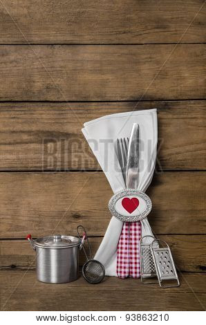 Menu card design for valentines, wedding or birthday party in red white checked with heart on wooden old background with cutlery.