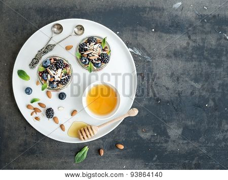 Yogurt oat granola with berries, honey and nuts in glass jars, dark grunge background
