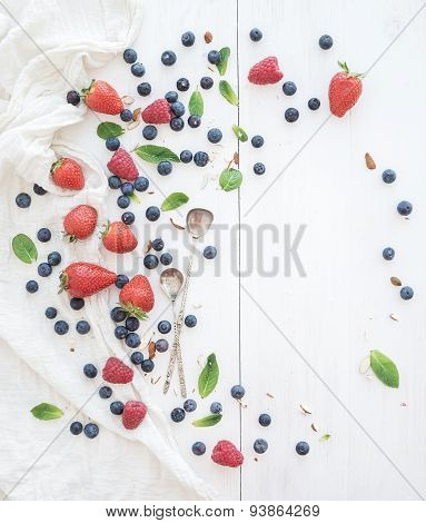 Berry frame with copy space on right. Strawberries, raspberries, blueberries and mint leaves, white
