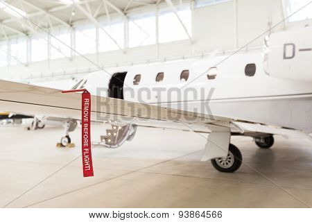 Airplane In Hangar With Remove Before Flight Labels In Red