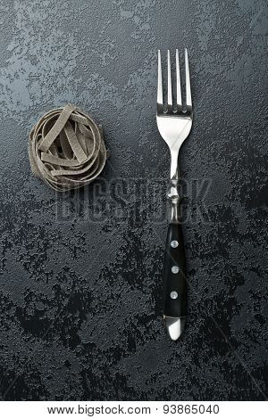 top view of black tagliatelle pasta and fork