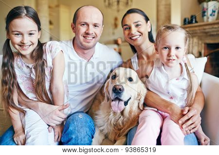 Cute siblings sitting on knees of their parents with dog near by