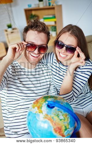 Amorous couple in sunglasses looking at camera with toothy smiles