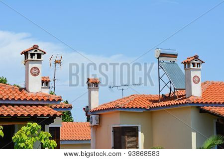 Typical Greek roofs with decorative chimneys and solar panel