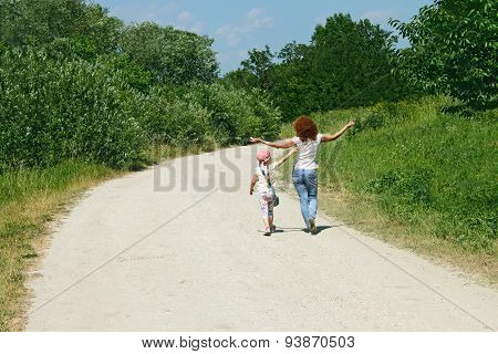 Mother And Daughter Walking By Rural Road