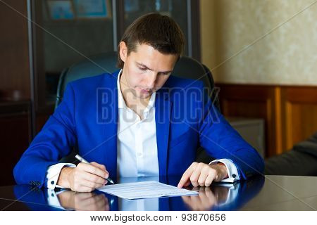 Business man signing a contract in big office
