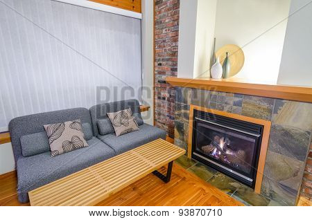 Interior design of a luxury living room with a brick wall and fireplace with a sofa and two pillows.