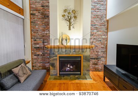 Interior design of a luxury living room with a brick wall and fireplace with a sofa and a pillow.