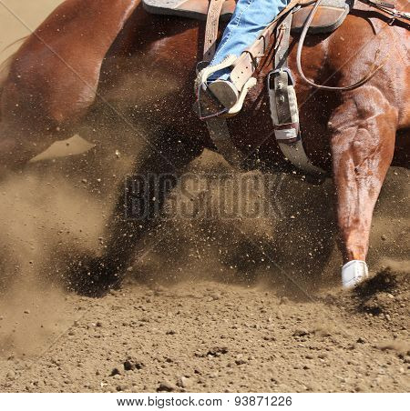 A horse sliding and kicking up dirt.