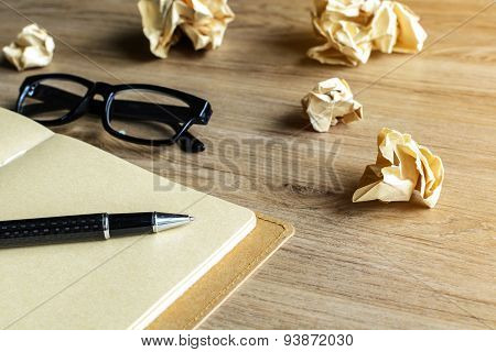 Crumpled Paper Balls With Eye Glasses And Notebook On Wood Desk