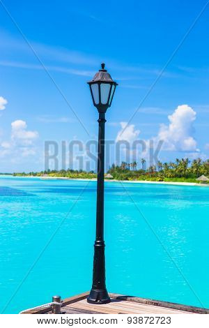 Lantern on the bridge at wooden pier with turquoise water at ideal island