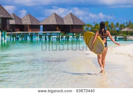 Young slender surf girl at white beach with yellow surfboard