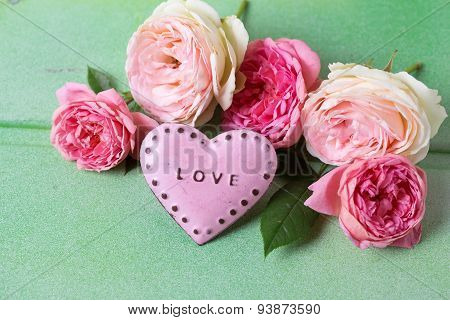 Blush Roses On Green Wooden Background.