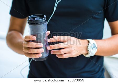 Close-up smart watch heart rate monitor and bottle of water in male hands